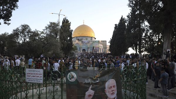 A banner depicting Hamas' leader Ismail Haniyeh is on display as Muslims gather for the Eid al-Fitr prayers at the Dome of the Rock Mosque in the Al-Aqsa compound in Jerusalem's Old City on Thursday 13 May 2021. - Sputnik International