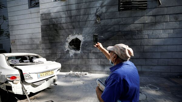 An Israeli man takes a photo with his mobile phone at a residential building after a rocket launched overnight from the Gaza Strip hit it in Ashkelon, Israel May 14, 2021. - Sputnik International