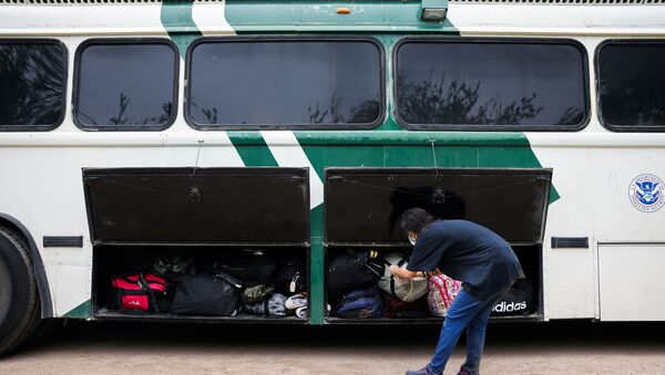 A migrant from Venezuela loads her belongings onto a border patrol bus after crossing the Rio Grande river into the United States from Mexico in Del Rio, Texas, U.S., May 11, 2021 - Sputnik International