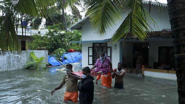 Police and rescue personnel evacuate local residents from a flooded house in a coastal area after heavy rains under the influence of cyclone 'Tauktae' in Kochi on May 14, 2021.  - Sputnik International