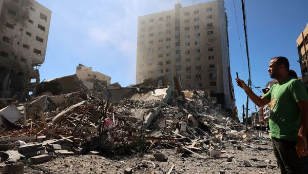 A Palestinian man takes a photograph with his mobile phone of a building hit and destroyed during an Israeli Air strike in Gaza City, on May 15, 2021. - Sputnik International