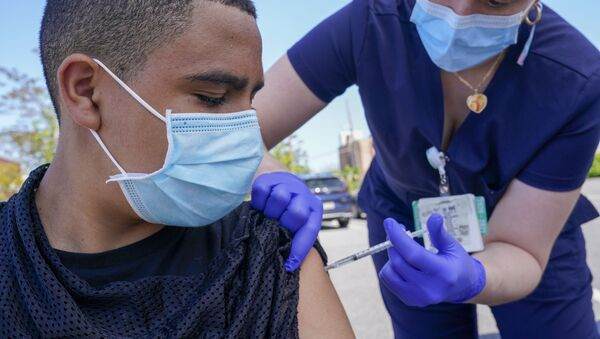 Justin Bishop, 13, watches as Registered Nurse Jennifer Reyes inoculates him with the first dose of the Pfizer COVID-19 vaccine at the Mount Sinai South Nassau Vaxmobile parked at the De La Salle School, Friday, May 14, 2021, in Freeport, N.Y.  - Sputnik International