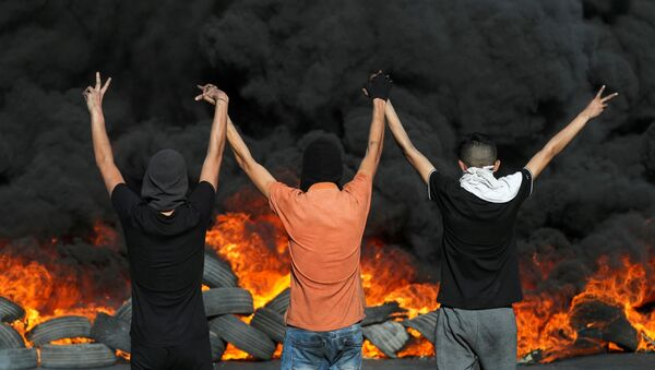 Palestinian demonstrators look at burning tires during a protest over tension in Jerusalem and Israel-Gaza escalation, in the Israeli-occupied West Bank, May 16, 2021. - Sputnik International