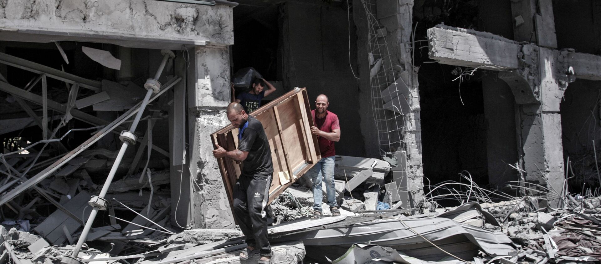 Palestinian men remove salvageable items from the bombarded Al-Jawhara Tower in Gaza City on May 17, 2021, five days after it was targeted by Israeli airstrikes. - Sputnik International, 1920, 17.05.2021
