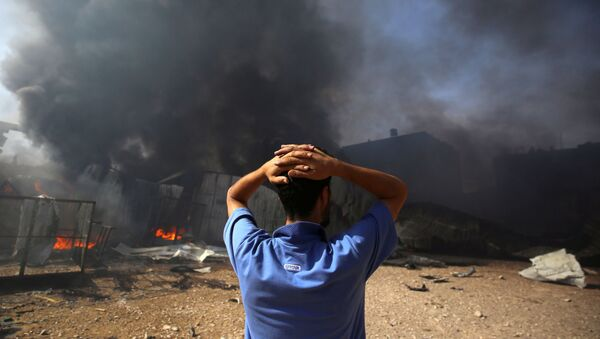 A man stands near a burning sponge factory after it was hit by Israeli artillery shells, according to witnesses, in the northern Gaza Strip May 17, 2021 - Sputnik International