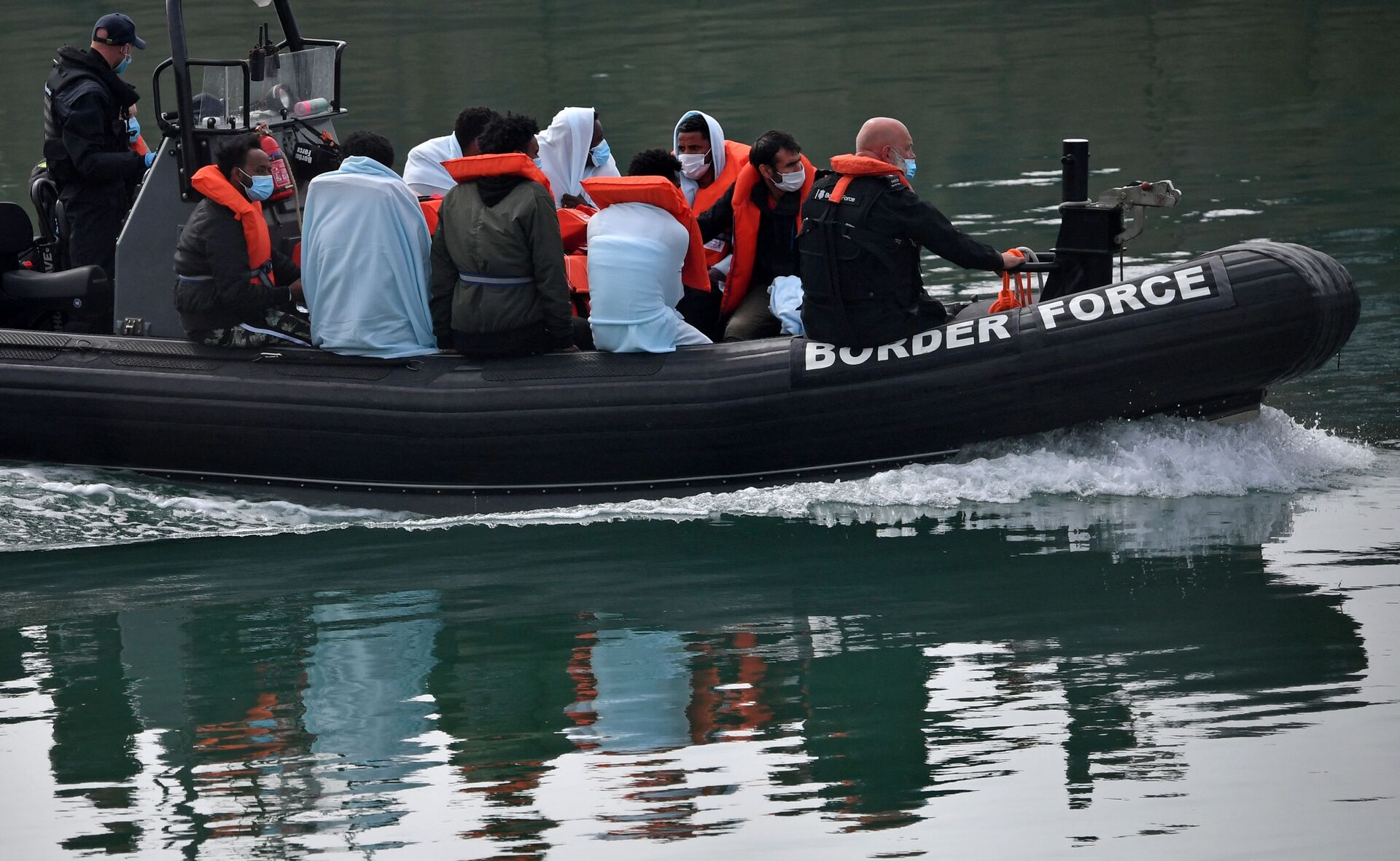 UK Border Force officials travel in a RIB with migrants picked up at sea whilst Crossing the English Channel, as they arrive at the Marina in Dover, southeast England on August 15, 2020 - Sputnik International, 1920, 20.09.2021