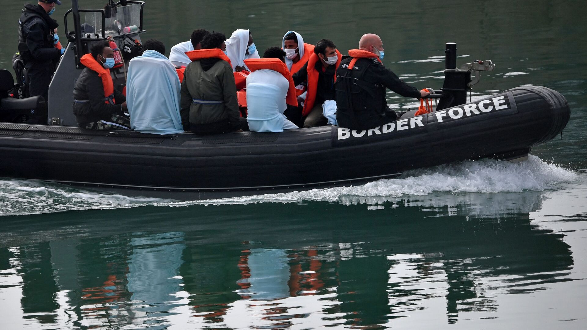 UK Border Force officials travel in a RIB with migrants picked up at sea whilst Crossing the English Channel, as they arrive at the Marina in Dover, southeast England on August 15, 2020 - Sputnik International, 1920, 24.07.2021