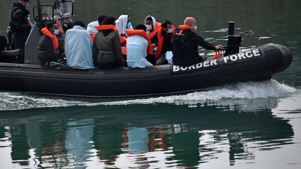 UK Border Force officials travel in a RIB with migrants picked up at sea whilst Crossing the English Channel, as they arrive at the Marina in Dover, southeast England on August 15, 2020 - Sputnik International