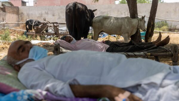 Villagers with breathing difficulties rest in cots as they receive treatment at a makeshift open-air clinic, amidst the spread of the coronavirus disease (COVID-19), in Mewla Gopalgarh village in Jewar district in the northern state of Uttar Pradesh, India, 16 May 2021 - Sputnik International
