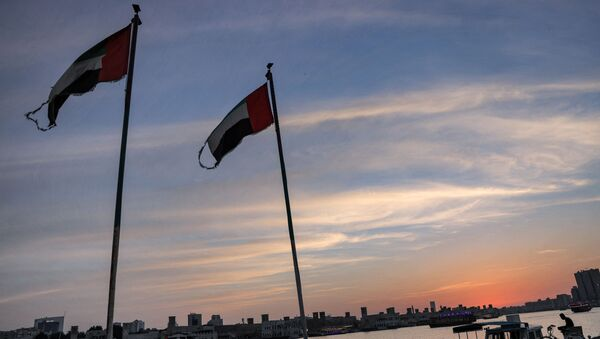 This picture taken on May 2, 2021 shows Emirati flags flying by boats moored along the Dubai creek at sunset. (Photo by GIUSEPPE CACACE / AFP) - Sputnik International