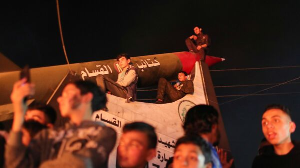 Palestinian demonstrators sit atop a monument of a Hamas rocket during an anti-Israel protest over tension in Jerusalem, in Gaza City April 24, 2021 - Sputnik International