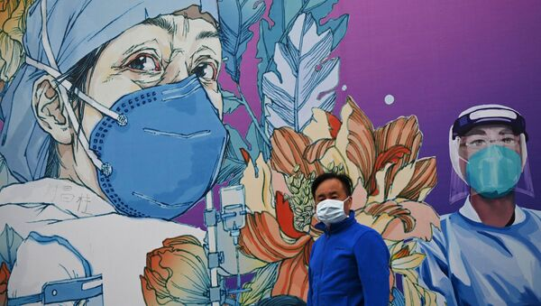 A man wearing a face mask walks in front of a mural at the Leishenshan Hospital that had offered beds for coronavirus patients in Wuhan, in China's central Hubei province on April 11, 2020 - Sputnik International