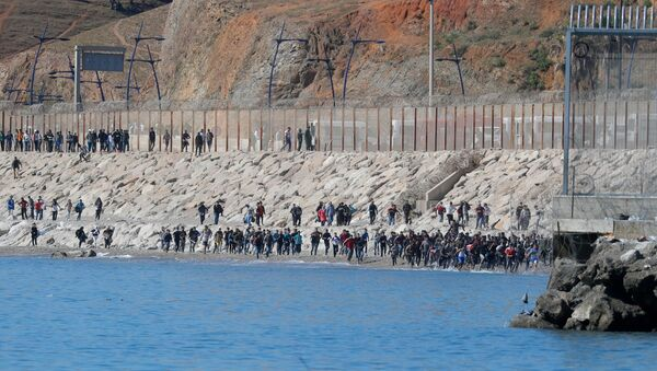Migrants run towards the fence separating Morocco from Spain, after thousands of migrants swam across the border, in Ceuta, Spain, May 19, 2021. REUTERS/Jon Nazca - Sputnik International
