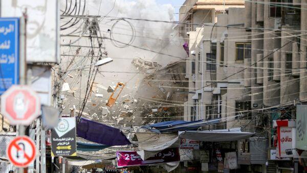 Debris fly as smoke rises following an Israeli air strike, amid Israeli-Palestinian fighting, in Khan Younis in the southern Gaza Strip, May 20, 2021. REUTERS/Ibraheem Abu Mustafa  - Sputnik International