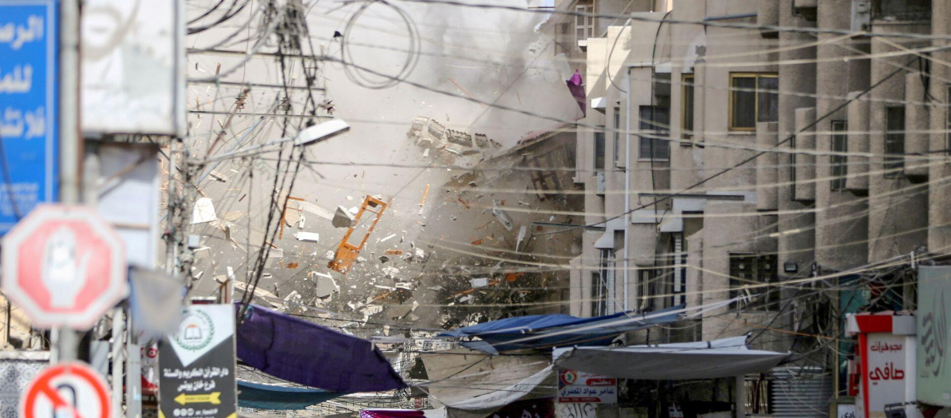 Debris fly as smoke rises following an Israeli air strike, amid Israeli-Palestinian fighting, in Khan Younis in the southern Gaza Strip, May 20, 2021. REUTERS/Ibraheem Abu Mustafa  - Sputnik International, 1920