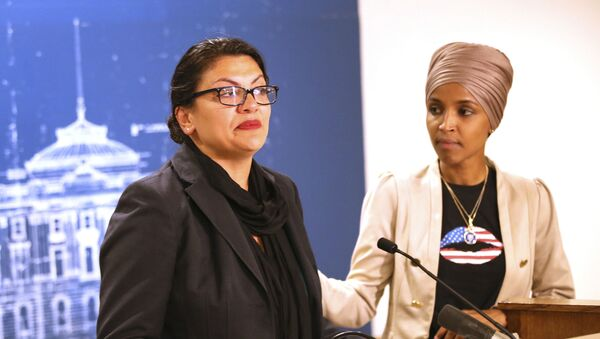 Rep. Ilhan Omar, right, (D-Minn) consoles Rep. Rashida Tlaib (D-MI) as she talk about Israel's refusal to allow them to visit the country during a news conference Monday, Aug. 19, 2019 at the State Capitol in St. Paul, Minn. - Sputnik International