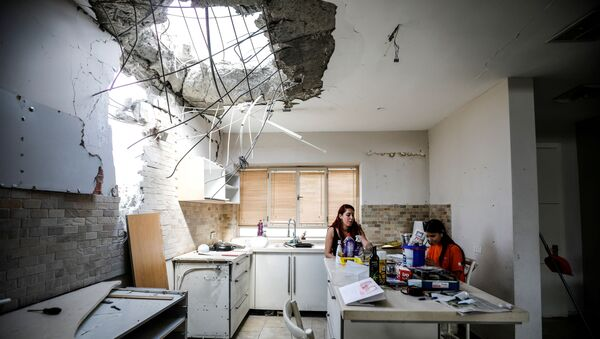 Family members of the Vaizel family, sit in the kitchen of their house which was damaged after it was hit by a rocket launched from the Gaza Strip earlier this week, in Ashkelon, Israel May 20, 2021 - Sputnik International