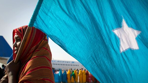 A woman holds the Somali flag at Mogadishu International Airport during a ceremony held 25 March to recieve the casket containing the body of fomer Somali president Abdullahi Yusuf Ahmed who died aged 77 at a hospital in the Gulf State of Abu Dhabi 23 March. Following the ceremony, Yusef's body was flown to his birthplace in Puntland where he was laid to rest - Sputnik International