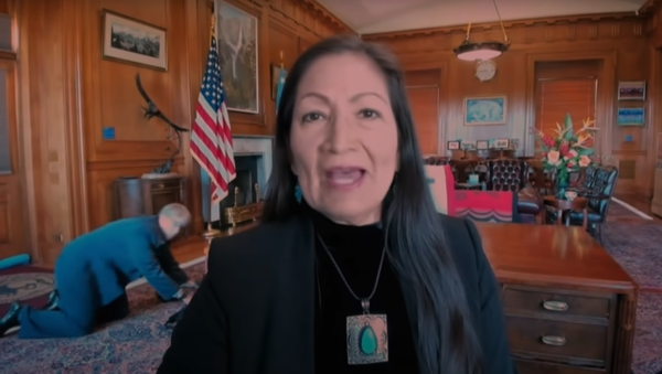 Late Night With Seth Meyers video clip screenshot showing a staffer crawling on the floor behind US Secretary of Interior Deb Haaland during the interview - Sputnik International