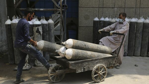 Workers load oxygen cylinders onto a hand cart to be carried inside the COVID-19 wards at a government-run hospital in Jammu, India, Friday, 7 May 2021 - Sputnik International