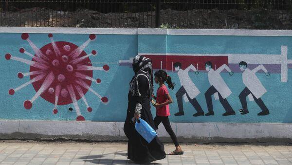 A woman along with a girl walk past a graffiti, depicting the coronavirus in Mumbai, India, Tuesday, April 6, 2021 - Sputnik International