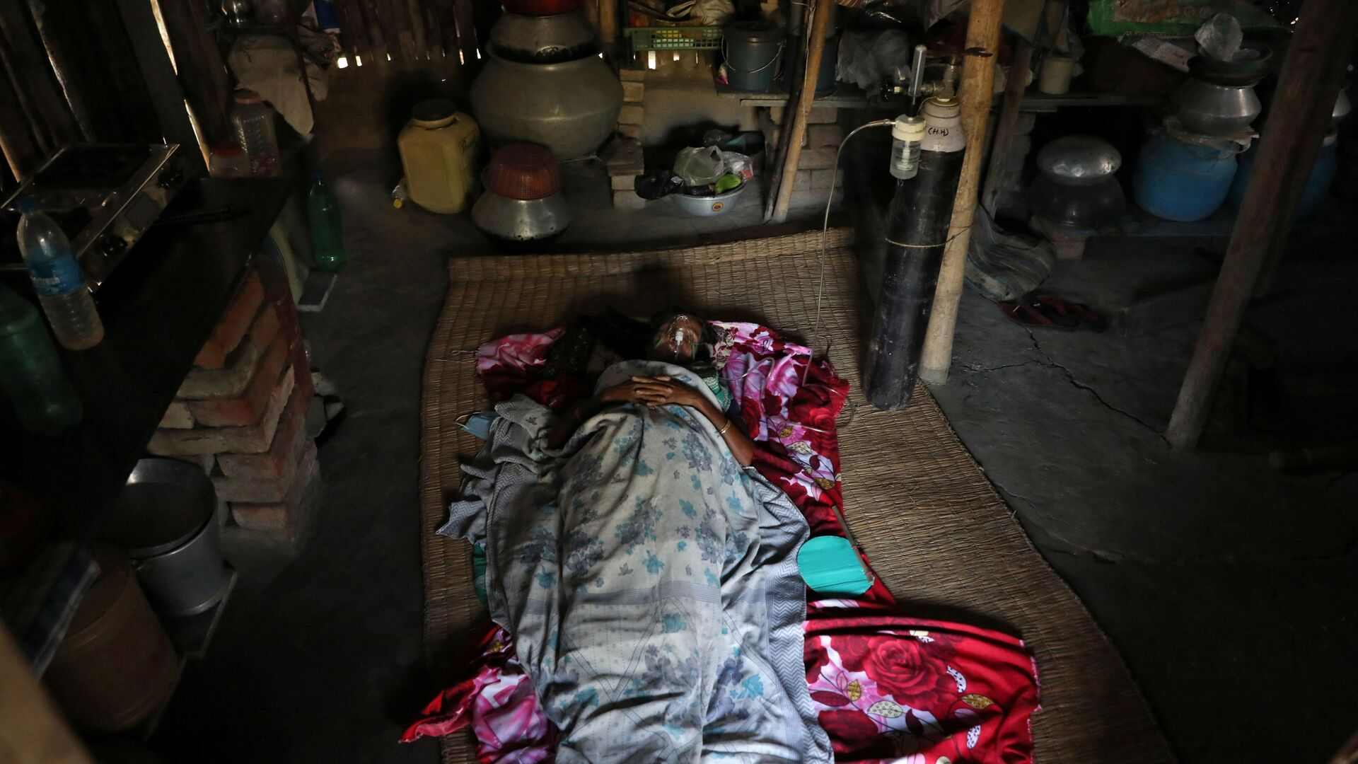 Parul Mondal, 50, a woman suffering from the coronavirus disease (COVID-19) receives oxygen support inside her house during a free medical camp set up to provide healthcare support to villagers, amidst the spread of the coronavirus disease (COVID-19), at Debipur village in South 24 Parganas district in the eastern West Bengal state, India, May 21, 2021 - Sputnik International, 1920, 22.09.2021