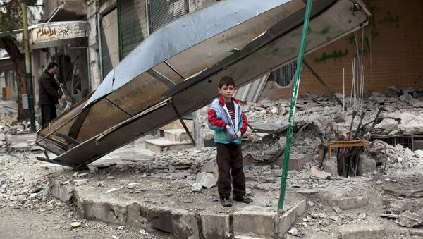 In this Monday, Feb. 27, 2012 file photo, a boy stands in from of a shop destroyed in Syrian Army shelling in the center of Idlib, in northern Syria. - Sputnik International