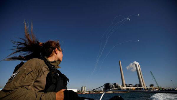 An Israeli soldier looks on as Israel's Iron Dome anti-missile system intercept rockets launched from the Gaza Strip towards Israel, as it seen from a naval boat patrolling the Mediterranean Sea off the southern Israeli coast as Israel-Gaza fighting rages on May 19, 2021 - Sputnik International
