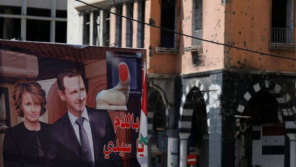 A view shows a banner depicting Syria's President Bashar al-Assad and his wife Asma, near a damaged building, ahead of the May 26 presidential election, in Homs, Syria May 23, 2021. - Sputnik International