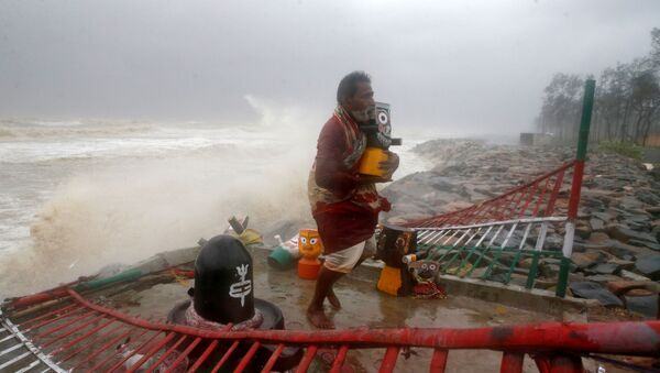 A Hindu priest carries an idol of Lord Jagannath from a seafront temple to a safer place ahead of Cyclone Yaas in Balasore district in the eastern state of Odisha India, May 26, 2021 - Sputnik International