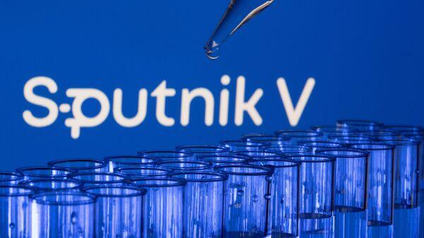 est tubes are seen in front of a displayed Sputnik V logo in this illustration taken, May 21, 2021. - Sputnik International