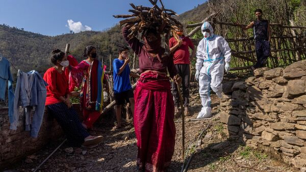 A healthcare worker wearing personal protective equipment (PPE), arrives to collect swabs from villagers to test them for COVID-19 (File). - Sputnik International