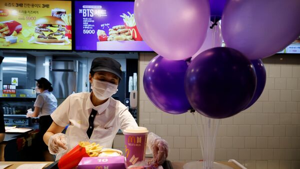 An employee of McDonald's serves a BTS meal, which is inspired and promoted by K-pop boy band BTS, during lunch hour at its restaurant in Seoul, South Korea, May 27, 2021 - Sputnik International