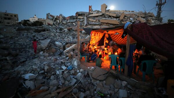 Palestinians from Zawaraa family hold candles as they sit in a makeshift tent amid the rubble of their houses which were destroyed by Israeli air strikes during the Israeli-Palestinian fighting in Gaza May 25, 2021. - Sputnik International