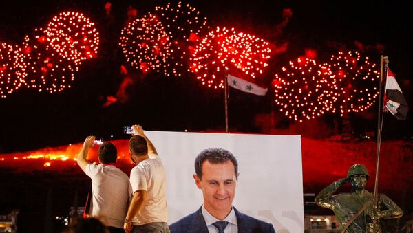 A poster depicting Syria's president Bashar al- Assad is seen as supporters of of Syria's President Bashar al-Assad celebrate after the results of the presidential election announced that he won a fourth term in office, in Damascus, Syria, May 27, 2021. - Sputnik International
