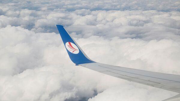 A wing of a plane of Belavia company is seen over clouds near Minsk, Belarus, July 19, 2016. - Sputnik International