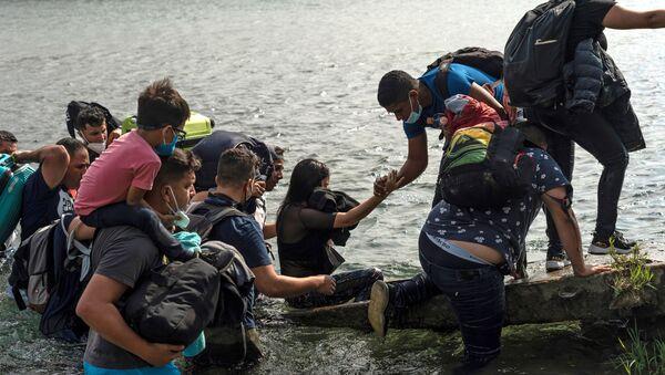 Asylum-seeking migrants cross the Rio Grande river in Del Rio - Sputnik International