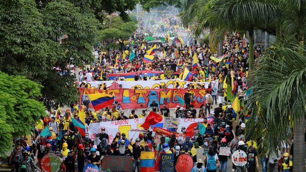 People take part in a protest demanding government action to tackle poverty, police violence and inequalities in healthcare and education systems, in Cali, Colombia May 28, 2021.  - Sputnik International