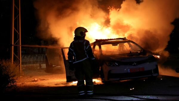 An Israeli firefighter stands near a burning Israeli police car during clashes between Israeli police and members of the country's Arab minority in the Arab-Jewish town of Lod, Israel May 12, 2021 - Sputnik International