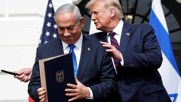 Israel's Prime Minister Benjamin Netanyahu stands with U.S. President Donald Trump after signing the Abraham Accords, normalizing relations between Israel and some of its Middle East neighbors,  in a strategic realignment of Middle Eastern countries against Iran, on the South Lawn of the White House in Washington, U.S., September 15, 2020. - Sputnik International