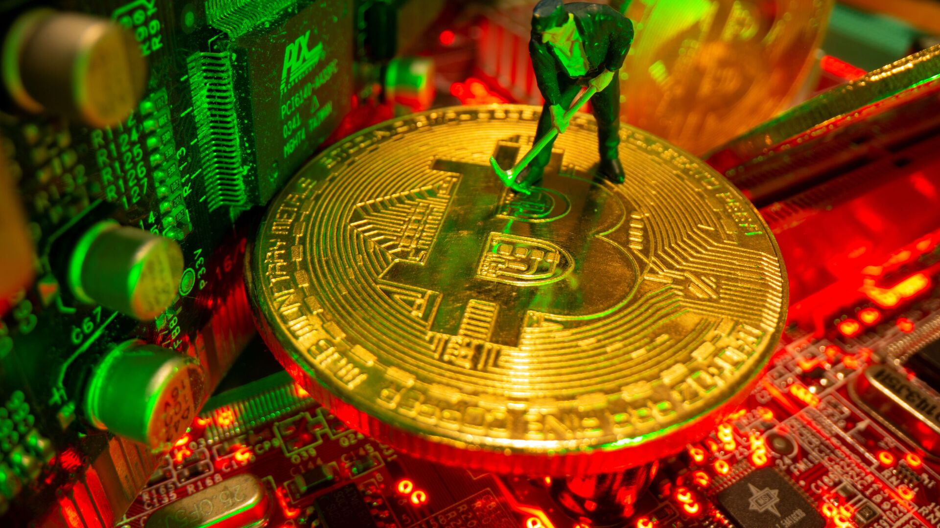 A small toy figure and representations of the virtual currency Bitcoin stand on a motherboard in this picture illustration taken May 20, 2021. - Sputnik International, 1920, 23.09.2021