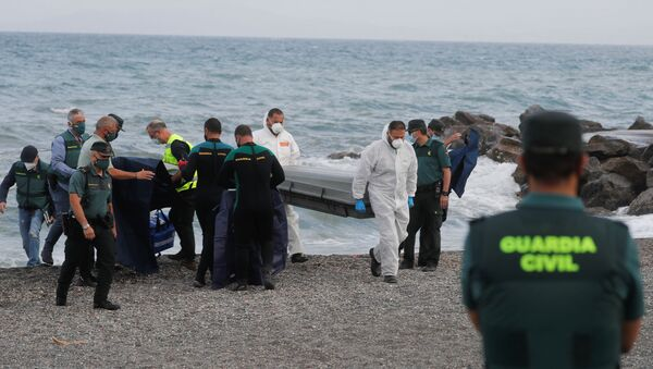 Workers carry a coffin containing a body at the shore near the Spanish-Moroccan border at El Tarajal Beach, after thousands of migrants swam across this border during the last days, in Ceuta, Spain, May 20, 2021 - Sputnik International