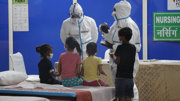 Doctors and health workers entertain children at a COVID-19 care center built in an indoor stadium in New Delhi, India, Monday, July 20, 2020 - Sputnik International