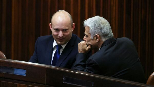 Yamina party leader Naftali Bennett smiles as he speaks to Yesh Atid party leader Yair Lapid, during a special session of the Knesset whereby Israeli lawmakers elect a new president, at the plenum in the Knesset, Israel's parliament, in Jerusalem June 2, 2021.  - Sputnik International
