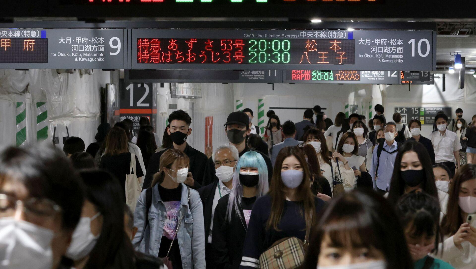 Commuters wearing protective face masks walk at a train station, amid the coronavirus disease (COVID-19) pandemic, in Tokyo - Sputnik International, 1920, 30.07.2021