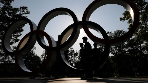 Visitors and the Olympic Rings monument are silhouetted outside the Japan Olympic Committee (JOC) headquarters near the National Stadium - Sputnik International