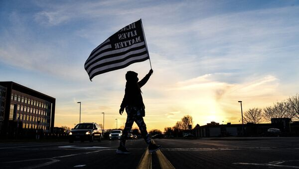 A demonstrator marches, holding a Black Lives Matter flag, during the sixth night of protests over the shooting death of Daunte Wright by a police officer in Brooklyn Center, Minnesota on April 16, 2021 - Sputnik International