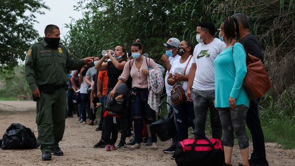 Migrants from Venezuela await transportation to a U.S. border patrol facility after crossing the Rio Grande river into the United States from Mexico in Del Rio, Texas, U.S., May 11, 2021 - Sputnik International