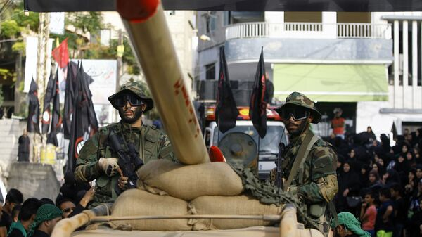 In this Sunday, Oct. 9, 2016 photo, Hezbollah fighters stand atop a car mounted with a mock rocket, as they parade during a rally to mark the seventh day of Ashoura, in the southern village of Seksakiyeh, Lebanon. - Sputnik International