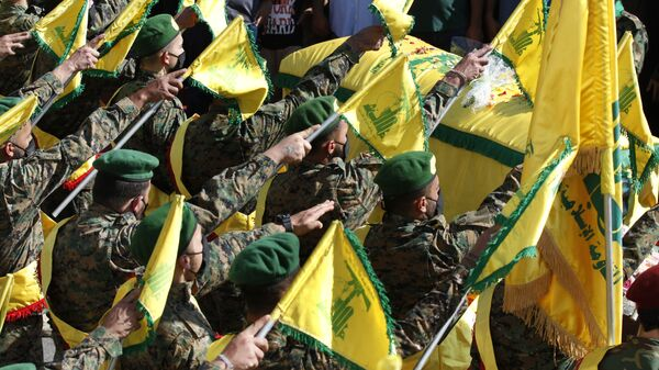 Hezbollah fighters raise their group flags, as they salut the coffin of their comrade Mohammed Tahhan who was shot dead on Friday by Israeli forces along the Lebanon-Israel border, during his funeral procession, in the southern village of Adloun, Lebanon, Saturday, May 15, 2021 - Sputnik International